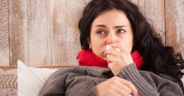 Frau mit Erkältung im Bett